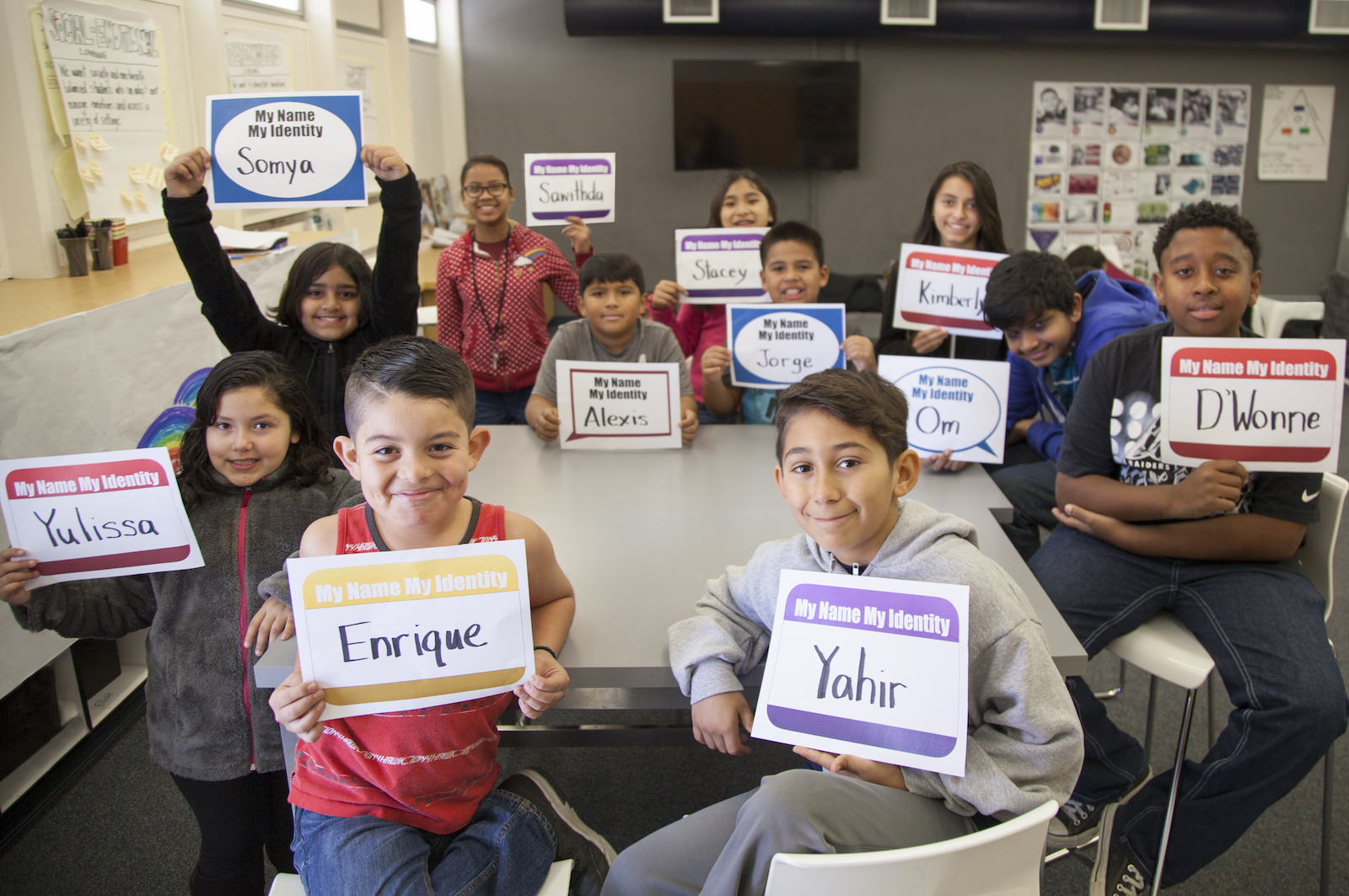Students in a classroom holding up signs with their names on them